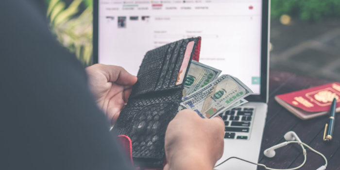 man sitting in front of a laptop and pulling hundred dollar bills out of a wallet